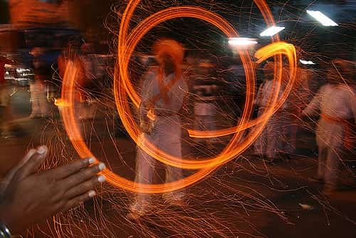 A maori practitioner fire spinning the poi