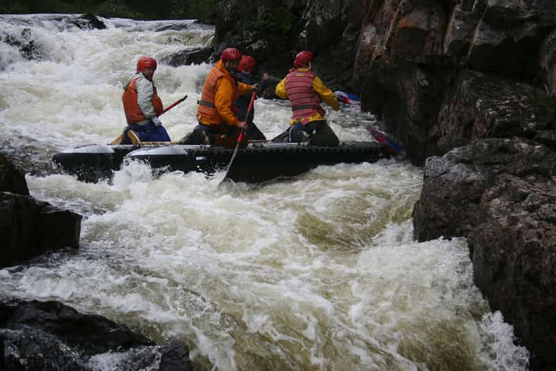 Adventure enthusiasts going through a rapid in the Kundalika river