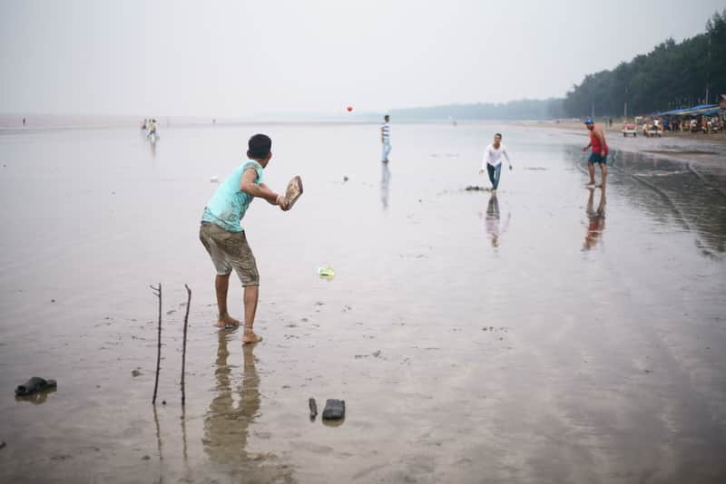 Kids playing cricket on a beach in Daman