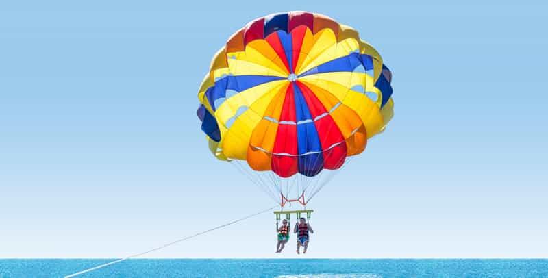 A couple parasailing off the coast of Marina Beach