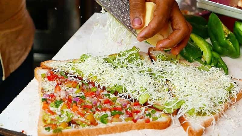 A vendor preparing a veg sandwich