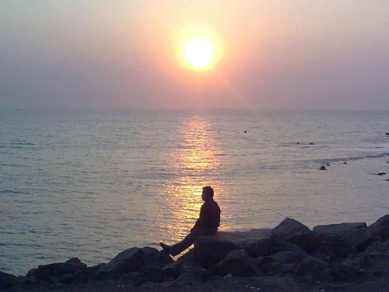 A visitor enjoying the sunset at Pirwadi Beach