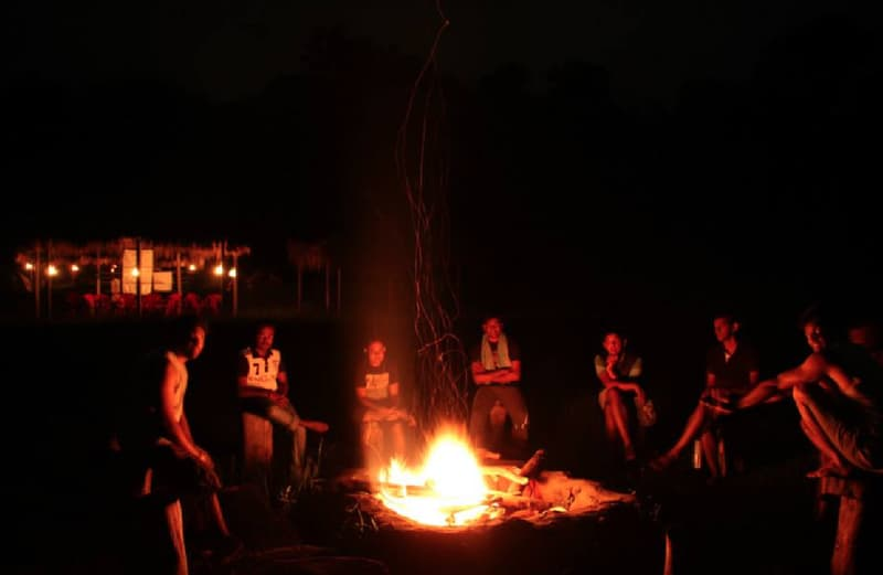 Campers by a bonfire in Coorg